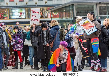 Group of protesters. Stockholm, Sweden - January 21 2017: Close up image of young caucasian female activists at a public square holding signs and about to join a demonstration. Store buildings in the background.