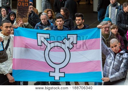 HBTQ flag and protesters. Stockholm, Sweden - January 21 2017: Close up image of a HBTQ flag and protesters. Multi ethnic group of people holding an HBTQ flag at public event at a public square to make a statement.