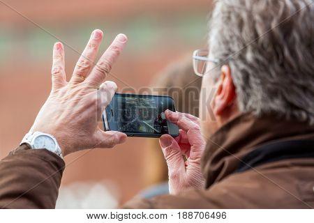 Senior hands holding smart phone. Stockholm, Sweden - January 21 2017: Close up image of senior male persons hands holding a mobile smart phone taking pictures. Blurred people seen on mobile screen.