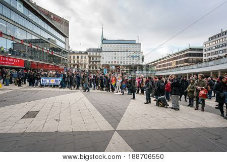 Stockholm, Sweden - January 21 2017: Low wide angle view of large group of people demonstrating at a public square holding flags and banners. City buildings in the background.