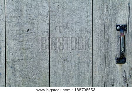 Closeup of old gray wooden door with old graffiti.