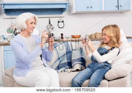 Grandmother and her granddaughter making photos or each other on photo cameras while staying at home. Lady making photos or videos on professional camera or mobile phone.