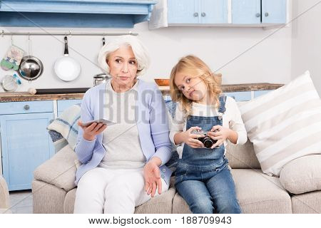 Difficulty of grandmother concerning understanding new computer technologies. Grandmother holding mobile or smart phone.