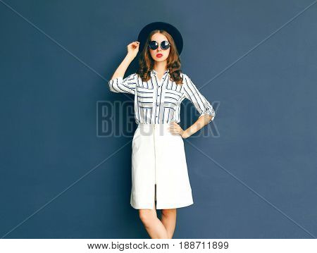 Fashion Elegant Lady Woman Wearing A Black Sunglasses, Hat And White Skirt Posing Over A Gray Backgr
