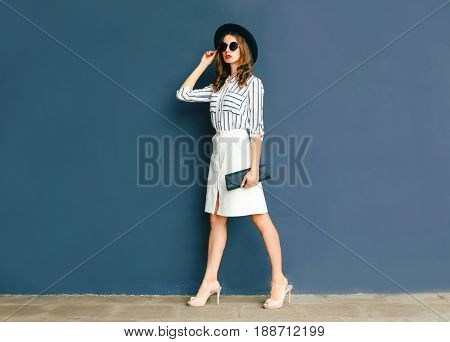 Fashion Elegant Woman Wearing A Black Hat And White Skirt With A Handbag Clutch Walking Over A Gray