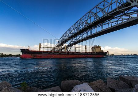 Port Huron, Michigan, USA - May 29, 2017: Great Lakes freighter travels under the twin spans of the Blue Water Bridge. The bridge connects Sarnia, Ontario in Canada to Port Huron, Michigan in the USA.