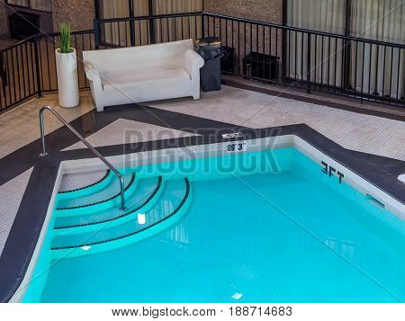 Indoor pool in a hotel, sofa and chairs on deck