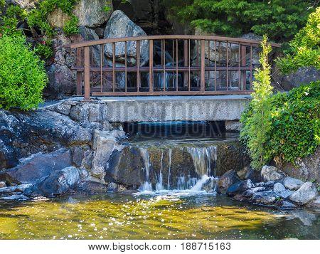Japanese garden design with water stream and bridge