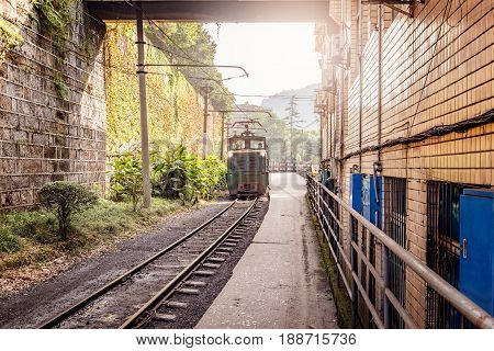 Electric narrow-gauge locomotive with the coal loaded freight train moves through Yuejin town to Shixi. Jiayang Mining Region. Sichuan province. China.