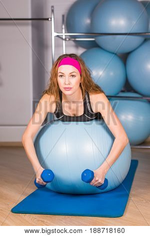 Woman exercising with dumbbells on a fitness ball.