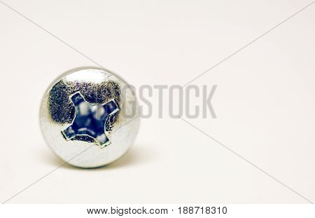 Stock close-up of shiney silver screw on plain white background