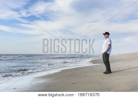 Mature Man Standing on Beach and Looking at Sea