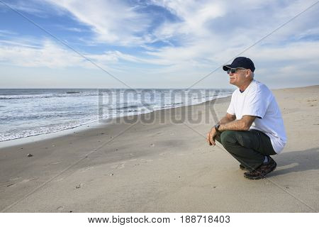 Mature Man Crouching on Beach Looking at Ocean