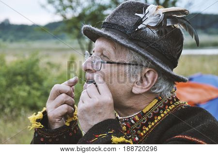 Drohobych Ukraine - June 29 2017: Ukrainian man in national dress playing the drymba Embroidery festival