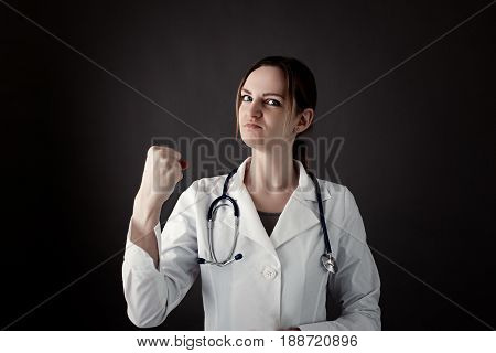 Female Intern Holds a fist and look in camera with strong face. Stethoscope or phonendoscope on neck. Medicine photo. Medical care or insurance concept. Professional doctor with pride emotion