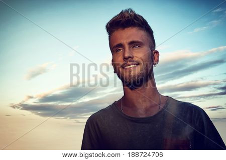 Handsome young man in against blue sky at sunset looking afar, shot from below