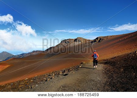 Tourist hiking in Haleakala volcano crater on the Sliding Sands trail. Beautiful view of the crater floor and the cinder cones below. Maui Hawaii USA.