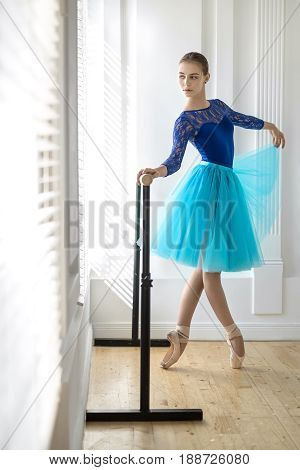 Pretty ballerina stands with crossed legs on pointes next to the ballet barre on the white wall background. She wears a lace blue leotard, cyan tutu, pointe shoes and looks to the side. Indoors.