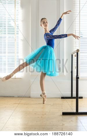 Attractive ballerina stands on the left toe next to the ballet barre on the white wall and windows background. She wears a lace blue leotard, cyan tutu, pointe shoes and looks into camera. Indoors.