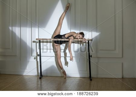 Amazing ballerina with closed eyes in a black leotard lies on the ballet bar while her right toe is on the floor and left leg is in the air. Backlighting in a form of star is on the wall behind her.