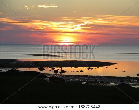 Colorful sunset photo with ocean, beach and land components.