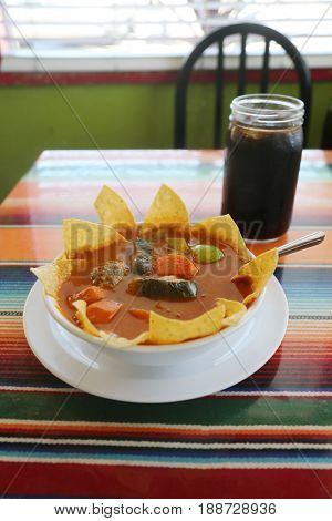 Traditional Mexican food mexican soup with meat balls and vegetables. Mexican  albondigas soup in a white ceramic bowl and plate on a traditional Mexican serape blanked table cloth and a spoon.