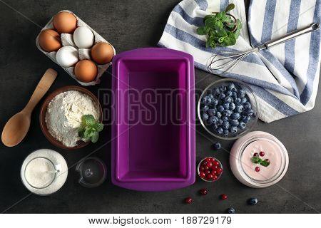 Silicone baking dish and ingredients for yogurt cake on grunge background