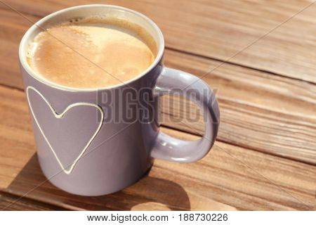 Cup with delicious coffee on wooden window sill