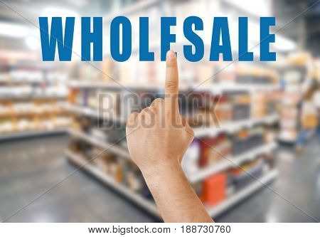 Wholesale concept. Male hand pointing on text and blurred background of shelves in supermarket