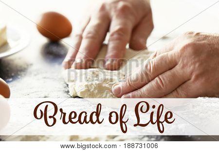 Text BREAD OF LIFE. Senior man kneading dough on table, closeup