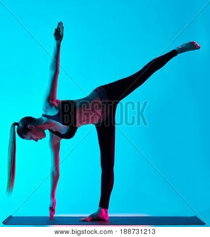 one caucasian woman exercising Ardha Chandrasana  half moon pose yoga exercices  in silhouette studio isolated on blue background