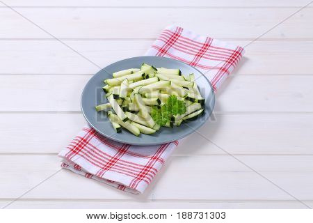 plate of zucchini strips on checkered dishtowel