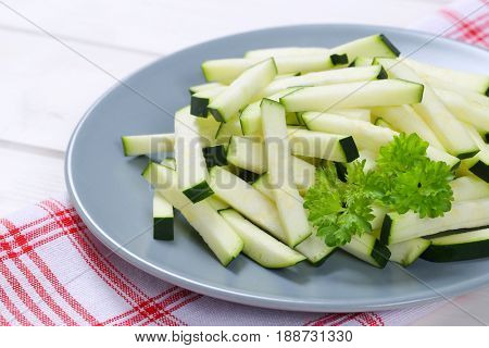 plate of zucchini strips on checkered dishtowel - close up