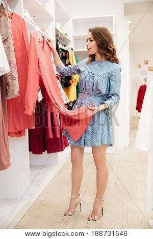 Image of happy young woman shopper in blue dress in shop choosing clothes. Looking aside.