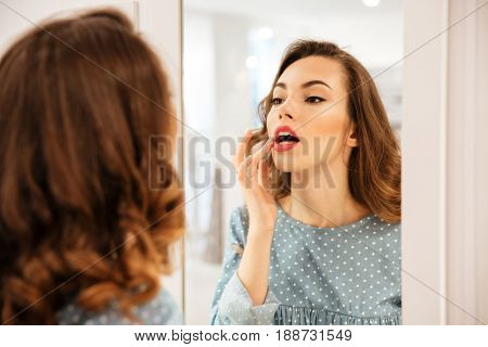Image of pretty young woman shopper in blue dress looking at mirror in shop. Looking aside.