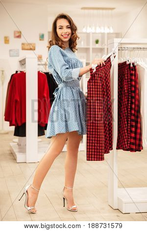 Image of cheerful woman shopper in blue dress choosing clothes in shop. Looking at camera.