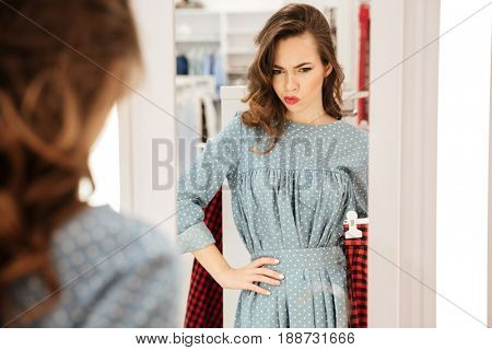 Photo of serious young woman shopper in blue dress looking at mirror in shop choosing clothes. Looking aside.