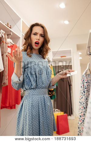 Surprised displeased woman looking camera while holding price of dress in shop