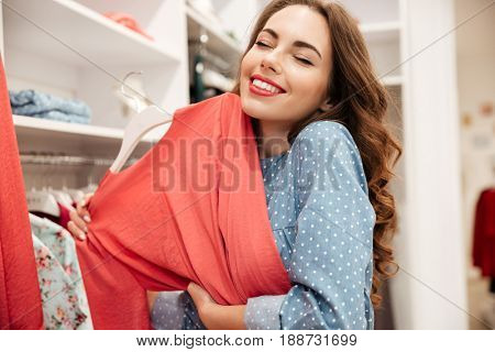 Picture of smiling young woman shopper in blue dress in shop choosing clothes. Eyes closed.