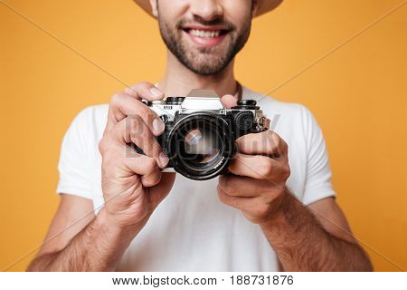 Close up shot of young cheerful man taking photo with old retro camera isolated over yellow