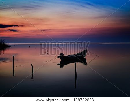 beautiful sunset/sunrise over water and silhouette fishing boat