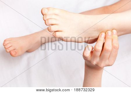 Elementary age girl's foot joint being manipulated by an osteopath - an alternative medicine treatment