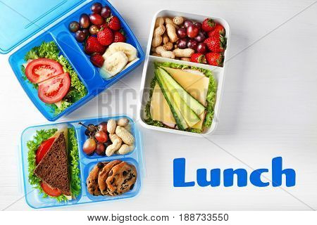 Concept of school lunch. Lunchboxes and food on wooden background