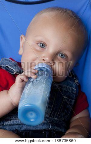 Caucasian baby boy in stroller drinking from bottle