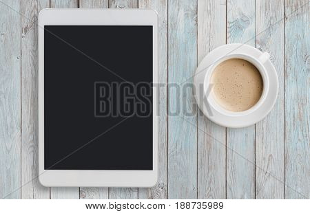 Tablet pc looking like ipad on table with coffee top view