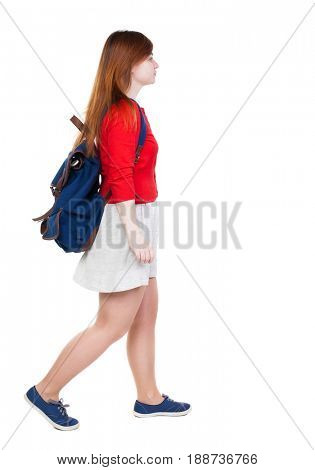 back view of walking  woman in dress with backpack.  girl in motion. backside view of person.  Rear view people collection. Isolated over white background. Young tourist in a white skirt goes to left.