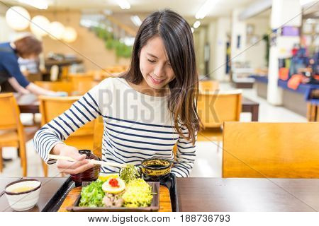 Woman eating soba in restaurant