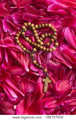 Rosary beads on flower background. Pray concept. Top view.