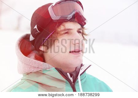 Young man wearing ski goggles outdoors