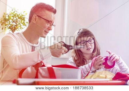 Father and daughter wrapping Christmas presents at home